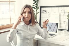 Young woman freelancer indoors home office concept formal style smartphone communication serious royalty free stock image