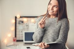 Young woman freelancer indoors home office concept winter atmosphere blurred background planning. Young female freelancer at home office winter standing close-up Stock Photo