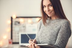 Young woman freelancer indoors home office concept winter atmosphere blurred background writing in planner smiling. Young female freelancer at home office winter Royalty Free Stock Photo