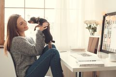 Young woman freelancer indoors home office concept winter atmosphere sitting with dog. Young female freelancer at home office winter sitting raising up toy royalty free stock image