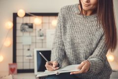 Young woman freelancer indoors home office concept winter atmosphere taking notes in planner close-up. Young female freelancer at home office winter sitting Royalty Free Stock Photo