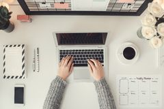 Young woman freelancer indoors home office concept winter atmosphere workplace top view. Young female freelancer at home office winter workplace top view typing royalty free stock photos