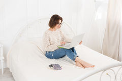 Young woman freelancer with laptop in bed, high key. Young woman freelancer works at home in bed with laptop. Engrossed Girl in eyeglasses. High key. Freelance Stock Images