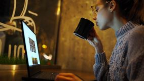 Young woman freelancer sitting at night in cafe and using laptop, looking at monitor and drinking coffee
