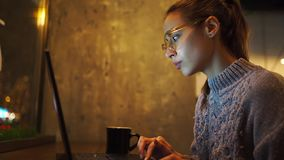 Young woman freelancer sitting at night in cafe and using laptop, looking at monitor