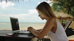 Young woman freelancer sitting at the sunbed with a laptop stock video footage