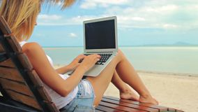 Young woman freelancer sitting at the sunbed with a laptop. Young woman sitting at the sunbed with a laptop in front of sunset view. Lady freelancer working at stock video footage