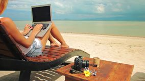 Young woman freelancer sitting at the sunbed with a laptop. Young woman sitting at the sunbed with a laptop in front of sunset view. Lady freelancer working at stock video
