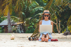 Young woman freelancer working in laptop on the beach. Freelance work. Young attractive woman in dress, sunglasses and hat, working in laptop on the beach, on stock photo