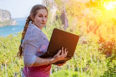 Young woman freelancer working with laptop on a top of the mountain with view on sea and tropical beach. Work and travel. On line stock images