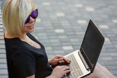 Young woman freelancing with laptop. Woman plus size walking outdoors with laptop in sunglasses. Freelancer works, looking for a client in internet, fulfilling stock photography