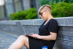 Young woman freelancing with laptop. Woman plus size walking outdoors with laptop in sunglasses, haircut is creative. Freelancer works, looking for a client royalty free stock image