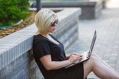 Young woman freelancing with laptop. Woman plus size walking outdoors with laptop in sunglasses, haircut is creative. Freelancer works, looking for a client royalty free stock photo