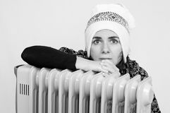 Young woman freezing near a heater Royalty Free Stock Photo