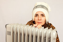 Young woman freezing near the heater. Studio shot Royalty Free Stock Photo