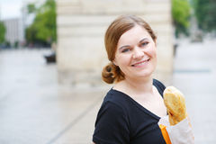 Young woman with fresh baguette on street of a city in France. Stock Image