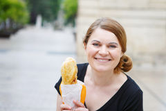 Young woman with fresh baguette on street of a city in France. Royalty Free Stock Images