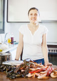 Young  woman with fresh marine products. In her kitchen Stock Photo