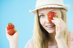 Young woman with fresh strawberries. Young positive woman playing with fresh strawberries fruits, on blue. Healthy meal Stock Photo