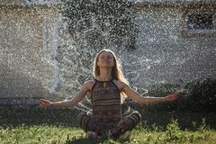 Young woman freshens up under bright waterdrops. From the irrigator stock image