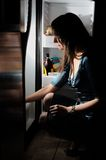 Young woman by a fridge. Young woman in a dress loking insede of fridge stock photos