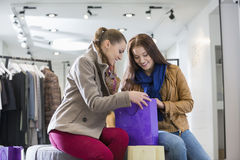 Young woman with friend looking into shopping bag at store Stock Photo