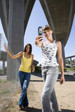 Young woman by friend, taking photograph beneath overpasses, smiling, portrait, low angle view Stock Images