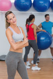 Young woman with friends in background at fitness studio Royalty Free Stock Photography