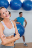Young woman with friends in background at fitness studio Royalty Free Stock Photo
