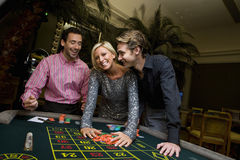 Young woman and friends gambling at roulette table, hands on chips, smiling, portrait Stock Photography