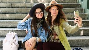 Young woman friends having fun, making face and taking selfies. Young woman friends having fun and taking selfies sitting on the stairs stock video footage