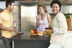 Young Woman With Friends At Kitchen Counter Royalty Free Stock Image
