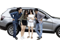 Young woman and friends lean on a car Stock Photo