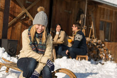 Young woman with friends snow winter cottage Stock Images