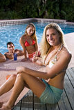 Young woman with friends by swimming pool Royalty Free Stock Images