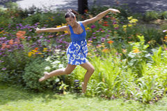Young Woman Frolicking on Grass. Beautiful young woman leaps on a grass lawn with bushes and flowers in the background. She is smiling at the camera. Horizontal Stock Images