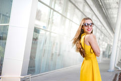 Young woman in front of airport in yellow dress Royalty Free Stock Photography
