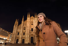 Young woman in front of Duomo in evening looking into distance Royalty Free Stock Images