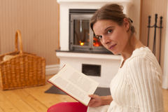 Young woman in front of a fire place Royalty Free Stock Images