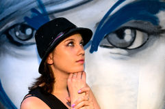 Young woman in front of graffito wall. Portrait of brunette girl in hat Stock Image