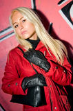 Young woman in front of graffito wall. Portrait of blonde girl in red Royalty Free Stock Photography