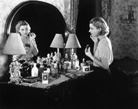Young woman in front of her vanity applying make-up. (All persons depicted are no longer living and no estate exists. Supplier grants that there will be no Royalty Free Stock Photo