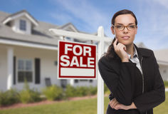 Young Woman in Front of House and Sale Sign. Attractive Mixed Race Woman in Front of House and For Sale Real Estate Sign Stock Photos