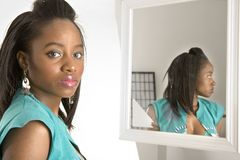 Young woman in front of a mirror royalty free stock photos