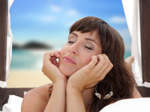 Young woman in front of the ocean. In a bed Stock Photo