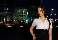 Young woman in front of office building at night Stock Photos
