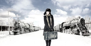 A young woman in front of an old railway. A young woman with heavy luggage in front of an old railway with two trains Stock Images