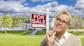 Young Woman in Front of For Sale Sign and House Stock Image