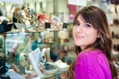 Young woman in front a shoes shop Royalty Free Stock Image