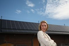 Young woman in front of solar-powered house. Young woman stand in front of a solar powered house and smile Stock Photo